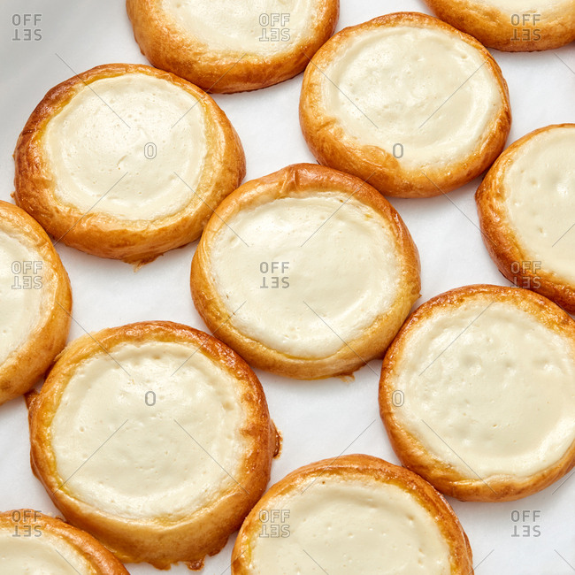 Delicious freshly baked small homemade cheese pies, vatrushka on a light gray background. Close up view. Flat lay.