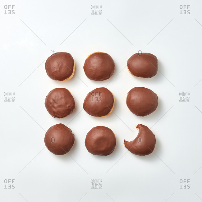 Food pattern with delicious homemade glazed chocolate doughnuts with one of them bitten at on a light gray background. Place for text. Top view.