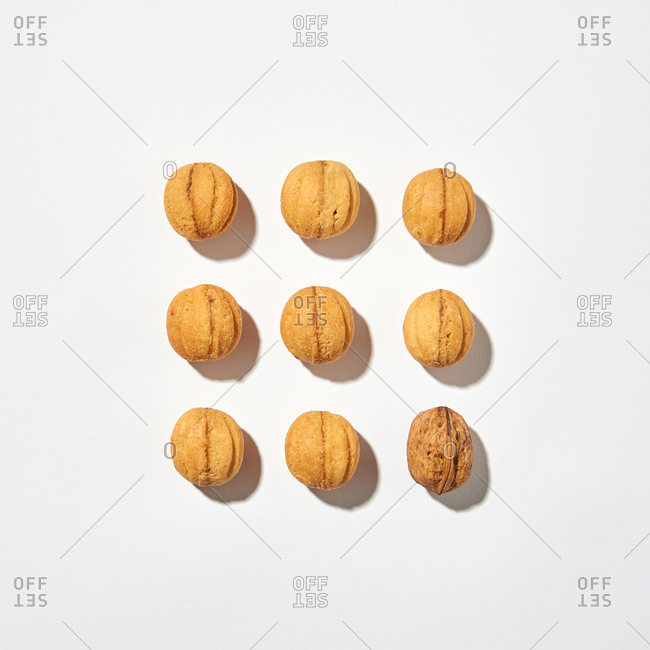 Bakery pattern square shape from homemade fresh cakes in a shape of nuts with shadows on a light gray background, copy space. Top view.