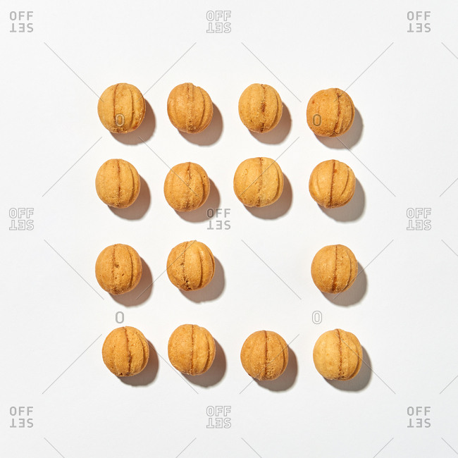 Baking composition with homemade delicious freshly baked cookies in the shape of walnuts of square form on a light gray background, hard shadows. Place for text. Flat lay.