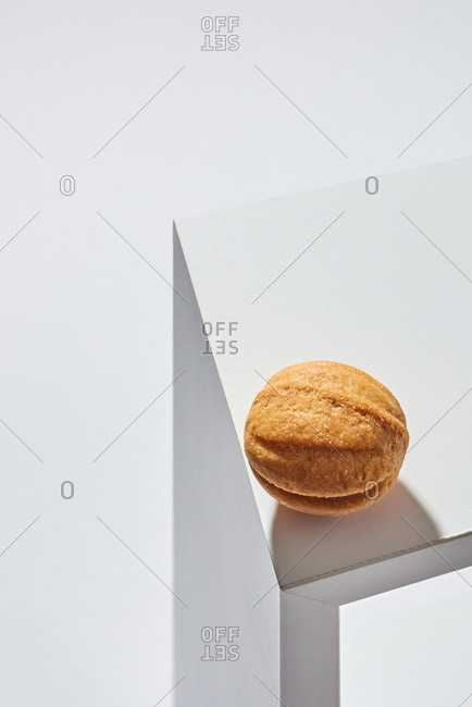 Small fresh tasty walnut cookie on the edge of gray table with hard shadows from it on a light background. Place for text.