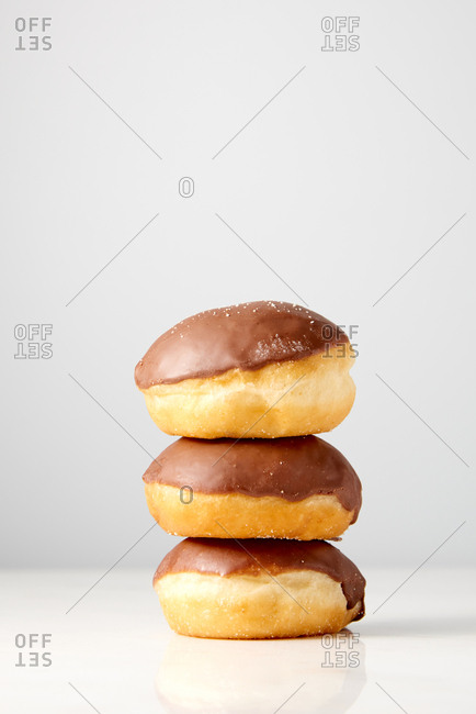 Fresh homemade doughnuts chocolate glazed in a heap on a light gray background with place for text. Concept of energy breakfast.