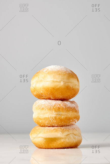 Fresh delicious homemade sugar icing doughnuts in a pile on a gray background. Place for text. Energy breakfast concept.