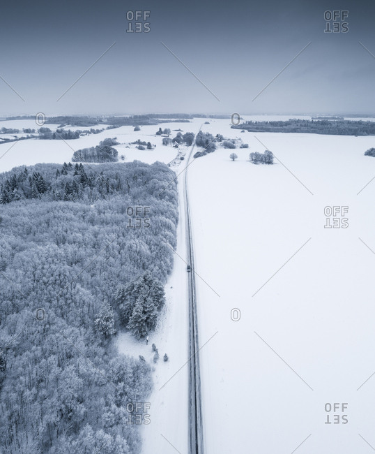 Car driving on a icy road next to the forest in snowy Estonian landscape.
