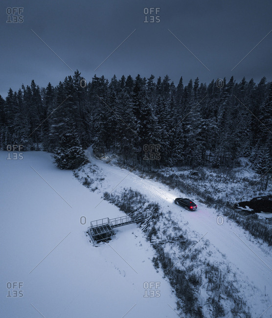 Snowy evening aerial view of a car stopping on a dam next to a river and lake in Estonia.