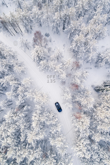 Aerial view of a car driving in the snowy Estonian forest.