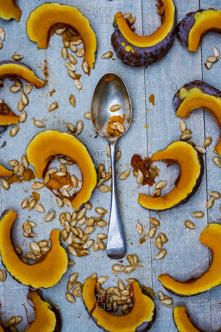 High angle close up of silver tablespoon and slices of pumpkin on blue background.