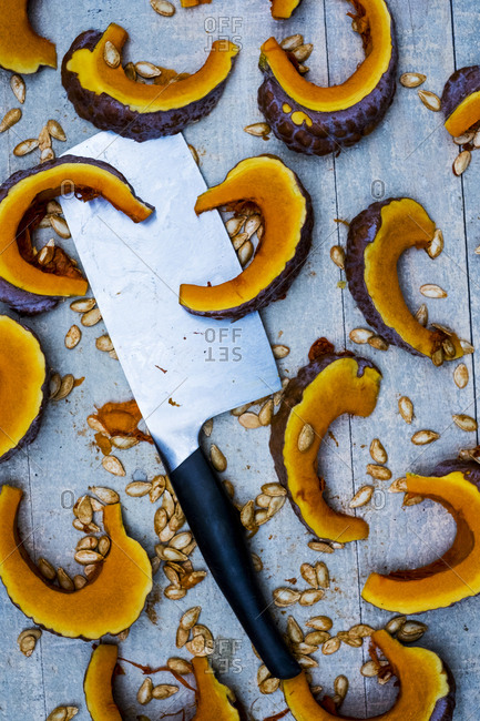 High angle close up of cleaver and slices of pumpkin on blue background.