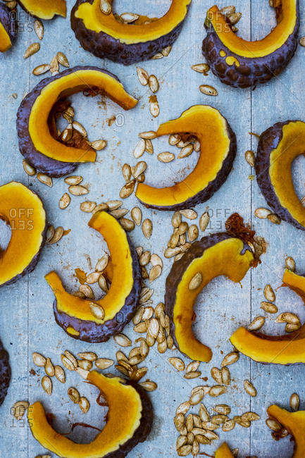 High angle close up of slices of pumpkin on blue background.