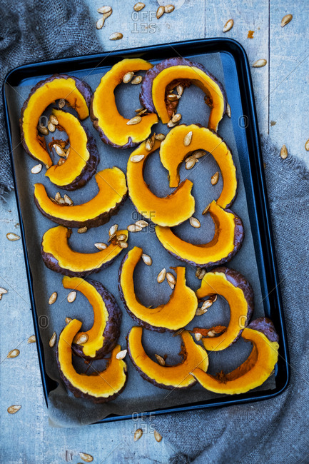 High angle close up of slices of pumpkin on a baking tray.