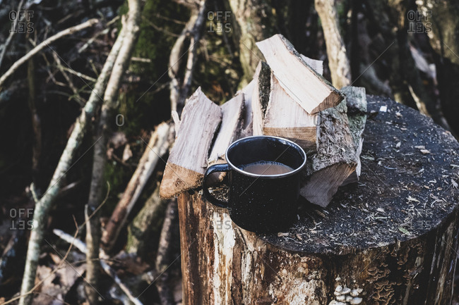 High angle close up of mug of tea and wooden logs on chopping block.