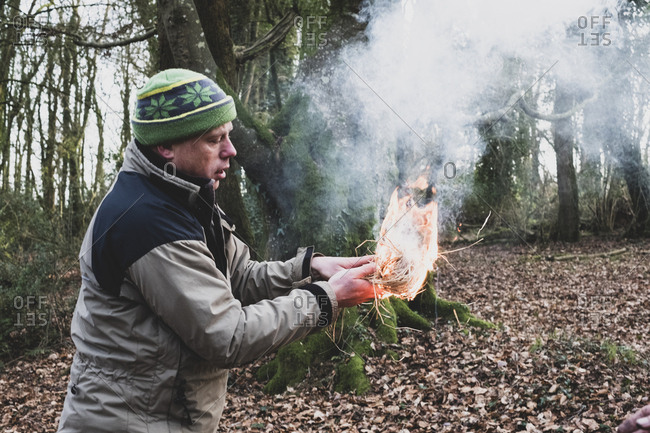 Man standing in a forest, holding lit-up bundle of straw, igniting fire.