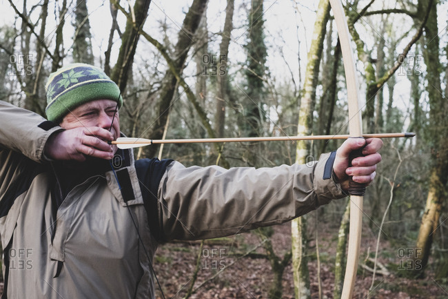 Close up of man standing in forest, using bow and arrow.