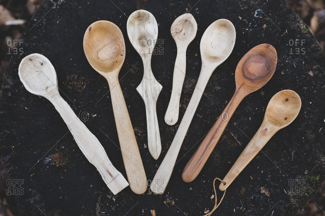 High angle close up of a selection of carved wooden spoons on chopping block.