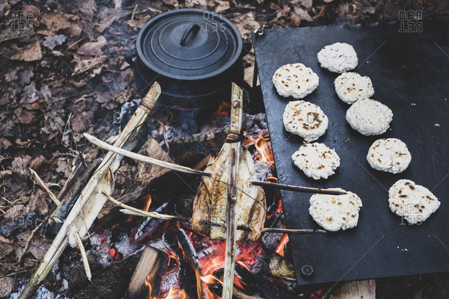High angle close up of fish on skewers and freshly made buns over a campfire.