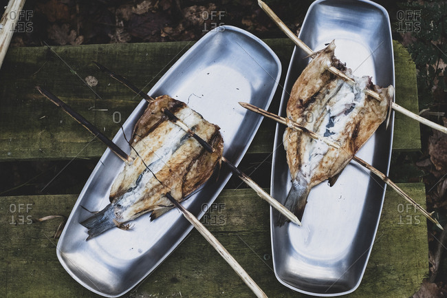 High angle close up of grilled fish on wooden skewers on metal plates, cooking outdoors