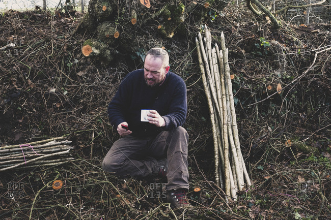 Bearded man sitting on ground next to bunch of wooden stakes, holding mug, checking his mobile phone.