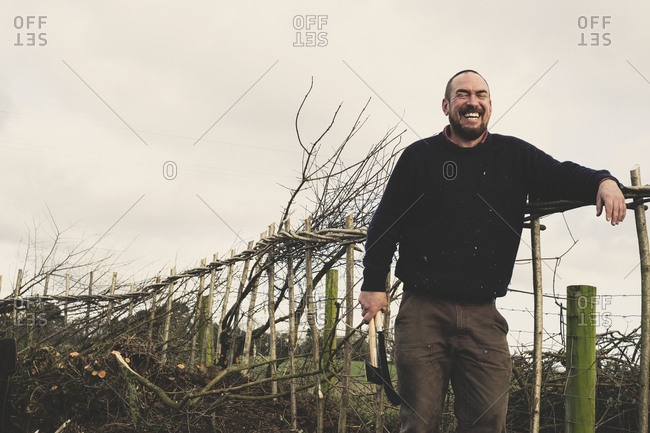 Bearded man holding axe and bill hook standing next to a newly built traditional hedge, laughing.