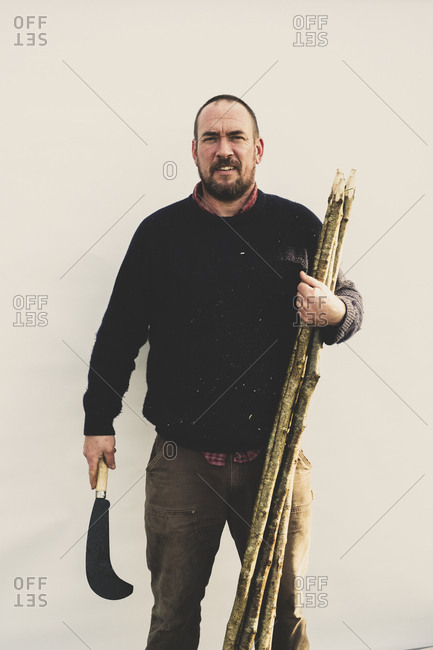 Bearded man holding bill hook and bunch of wooden stakes for traditional hedge laying, smiling at camera.