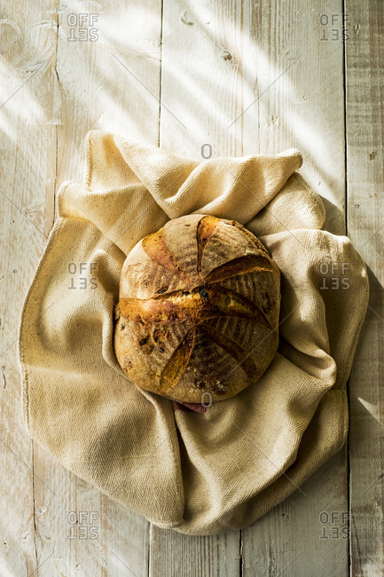 High angle close up of a freshly baked round loaf of bread on tea towel.