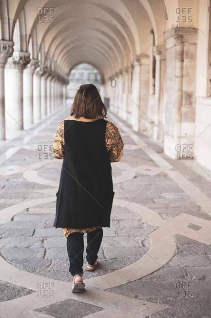 Rear view of woman walking along a colonnade in Venice, Veneto, Italy.