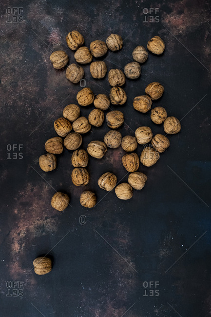 High angle close up of walnuts on black rusty surface.