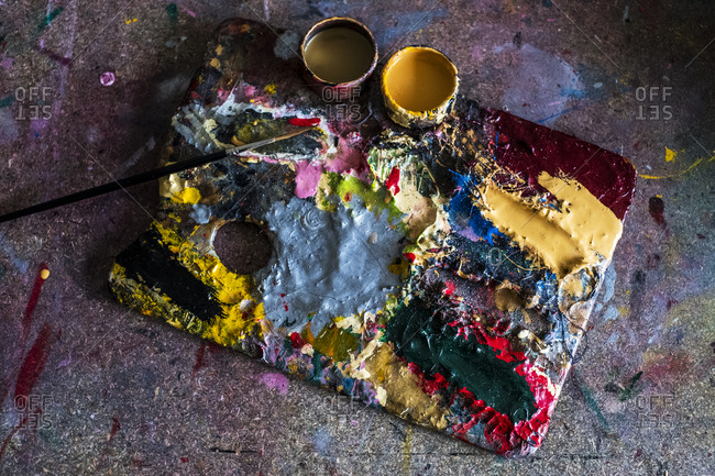 High angle close up of painter's palette, oil paints and paintbrush in a workshop.