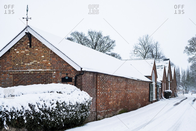 Exterior view of red brick cottages with snow-covered roofs along a rural road.