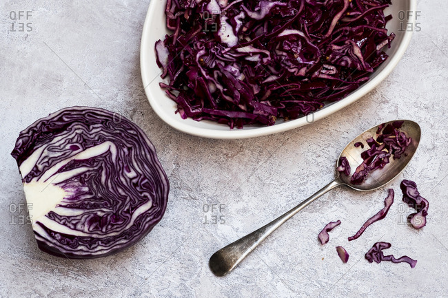 A dish of cooked red cabbage and half a raw cabbage.