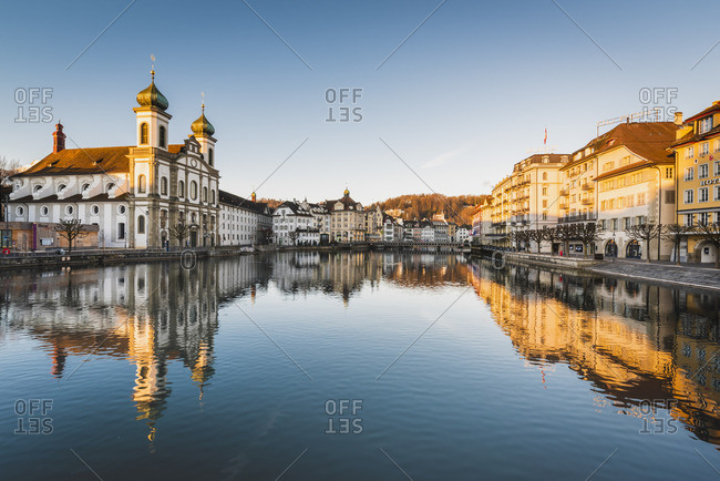 February 17, 2019: Lucerne, Switzerland. Jesuit church and Reuss river's waterfront at sunrise