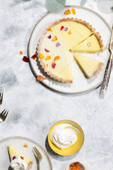 Overhead view of fresh lemon tart with edible flower petals and whipped cream
