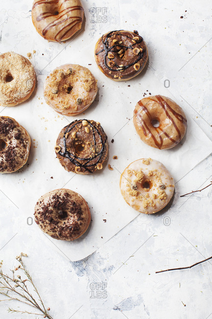 Nine uniquely decorated yeast donuts on a marble countertop