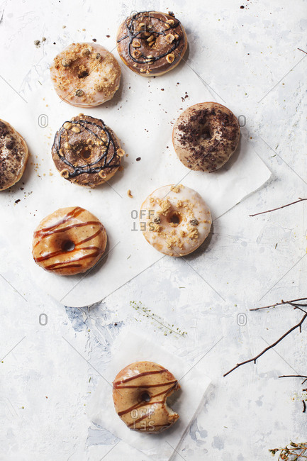 Eight yeast donuts with unique toppings on parchment paper