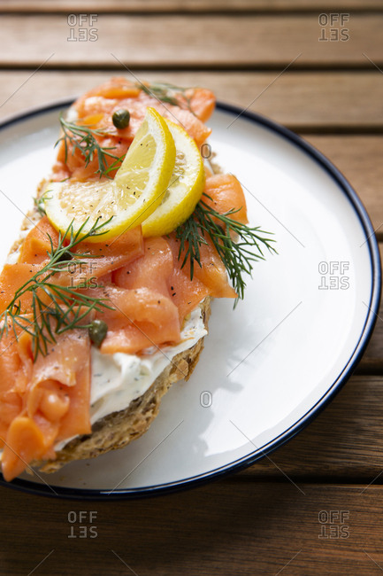 Sliced salmon and cream cheese with capers, herbs and lemons
