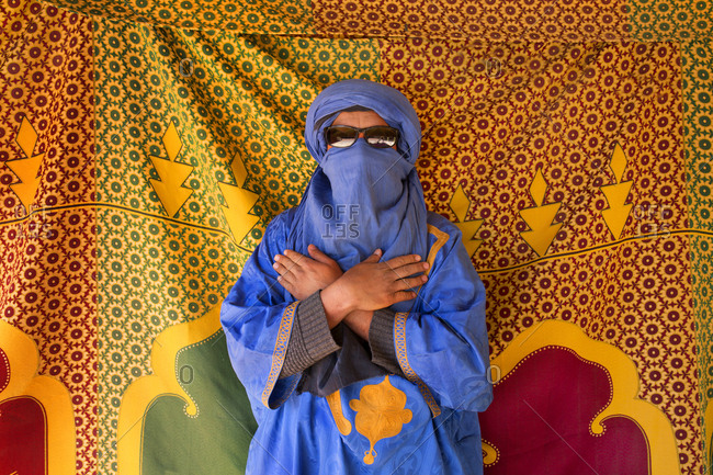 Portrait of a Tuareg nomad man against a fabric backdrop in the Erg Chebbi sand dune region of Merzouga, Morocco