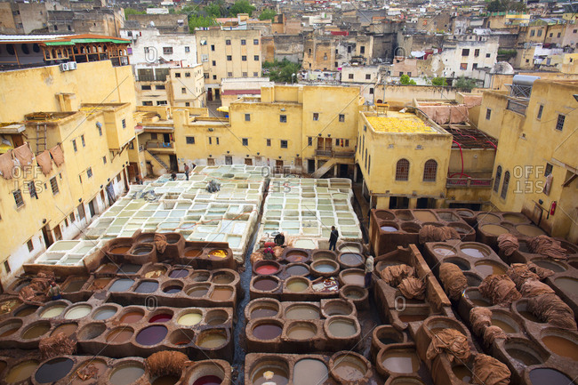Fes, Morocco - April 6, 2019: Wide angle view of workers in a leather tannery and pots of various color dyes