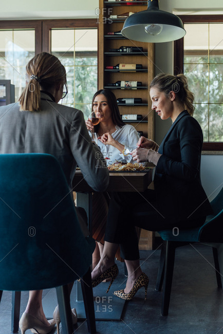 Three business women have lunch at a restaurant