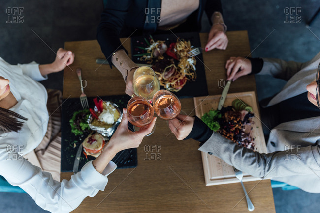 Overhead of three women drinking wine at lunch