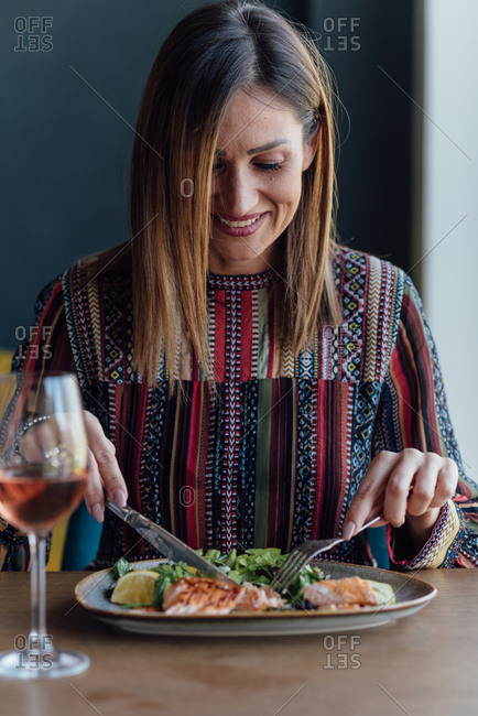 Beautiful woman enjoys a glass of wine with her lunch