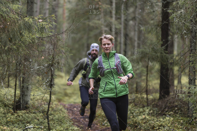 Man and woman running in forest