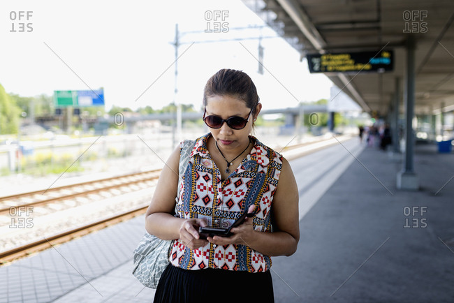 Woman on train station looking at cell phone