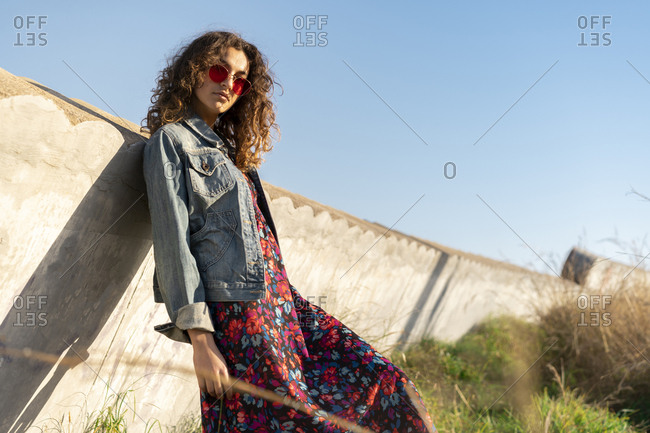 Portrait of young woman with curly brown hair wearing red sunglasses leaning against wall
