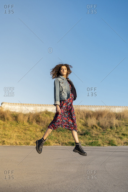 Portrait of young woman with curly brown hair jumping in the air