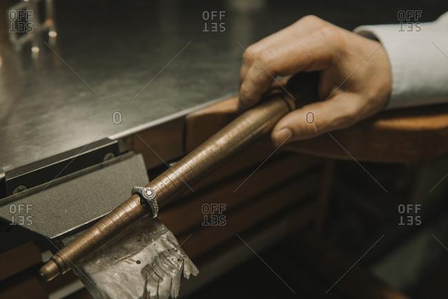 Artisan making jewelry in his workshop- measuring ring