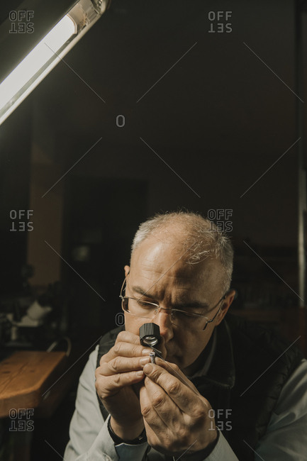 Artisan looking at ring with gemstone- portrait