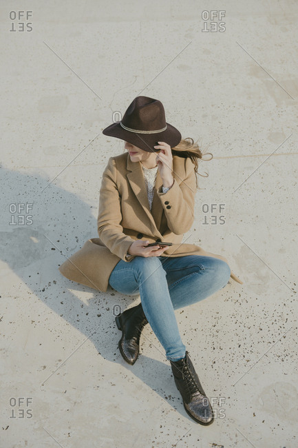 Young hipster woman sitting on the ground holding a phone