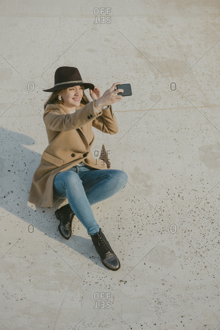 young hipster woman sitting on the ground making a selfie