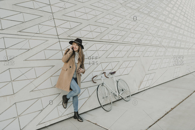 Young hipster woman speaking by phone near to a bicycle