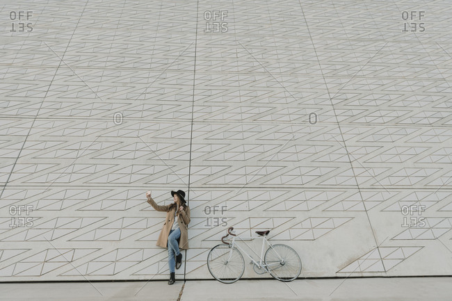 Young hipster woman near to a bicycle making a selfie