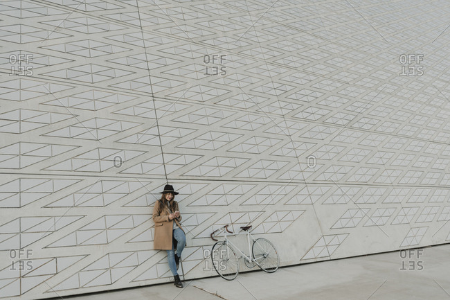 Young hipster woman holding smartphone near to a bicycle